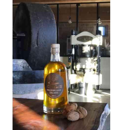 """Huile de noix """"mordorée"""" (50cl) - L'huile La Vie Contée à noix nue s'élabore, fruitée ou mordorée, précieux filet d'or...  Notre huile de noix vierge """"mordorée"""" est fabriquée dans le respect de la méthode traditionnelle du Périgord, artisanale et « 100% mécanique ».  C'est dans le chaudron en fonte que se fait le goût d'une huile pressée à chaud ! Après écrasement des cerneaux sous la meule, la pâte de noix est progressivement montée en température jusqu'à 110°C dans le chaudron en fonte pour que l'huile de noix « mordorée » offre en bouche un goût intense de noix toastée ! L'huile repose ensuite deux semaines, ce qui lui permet de décanter naturellement, sans filtration mécanique.  Pour explorer les nuances incroyables de goût et de texture de la pressée à chaud en Périgord, nous vous proposons de découvrir notre triplette de """"chaleureuses"""" : la fine douceur de la """"fruitée"""", le goût légèrement grillé de l'""""adorée"""" (AOC huile de noix du Périgord) ou le toasté plus intense de la """"mordorée"""".  L'huile de noix de la Vie Contée conditionnée en bouteille en verre de 50 cl (ou en bidon métallique alimentaire de 25 cl).  Composition : 100% huile de noix.  Conseils de dégustation L'huile de noix du moulin de La Vie Contée est parfaite pour l'assaisonnement de salades, mais aussi sur des viandes rouges tel que le magret de canard, ou encore sur des poissons en versant un filet d'huile au moment de servir : par exemple, l'huile de noix peut se substituer aux amandes pour revisiter une truite de manière subtile. Elle peut également apporter des notes douces aux veloutés (de potimarron par exemple) ou encore aux gaspachos (très original sur des épinards ou du cresson). Enfin, le gâteau au yaourt « 100% huile de noix » est immanquable pour les enfants.  Conservation Il est fortement recommandé de conserver l'huile à l'abri de la lumière, et de ne pas l'exposer à une température excédant une vingtaine de degrés.  Crédit photo : Anaka"""